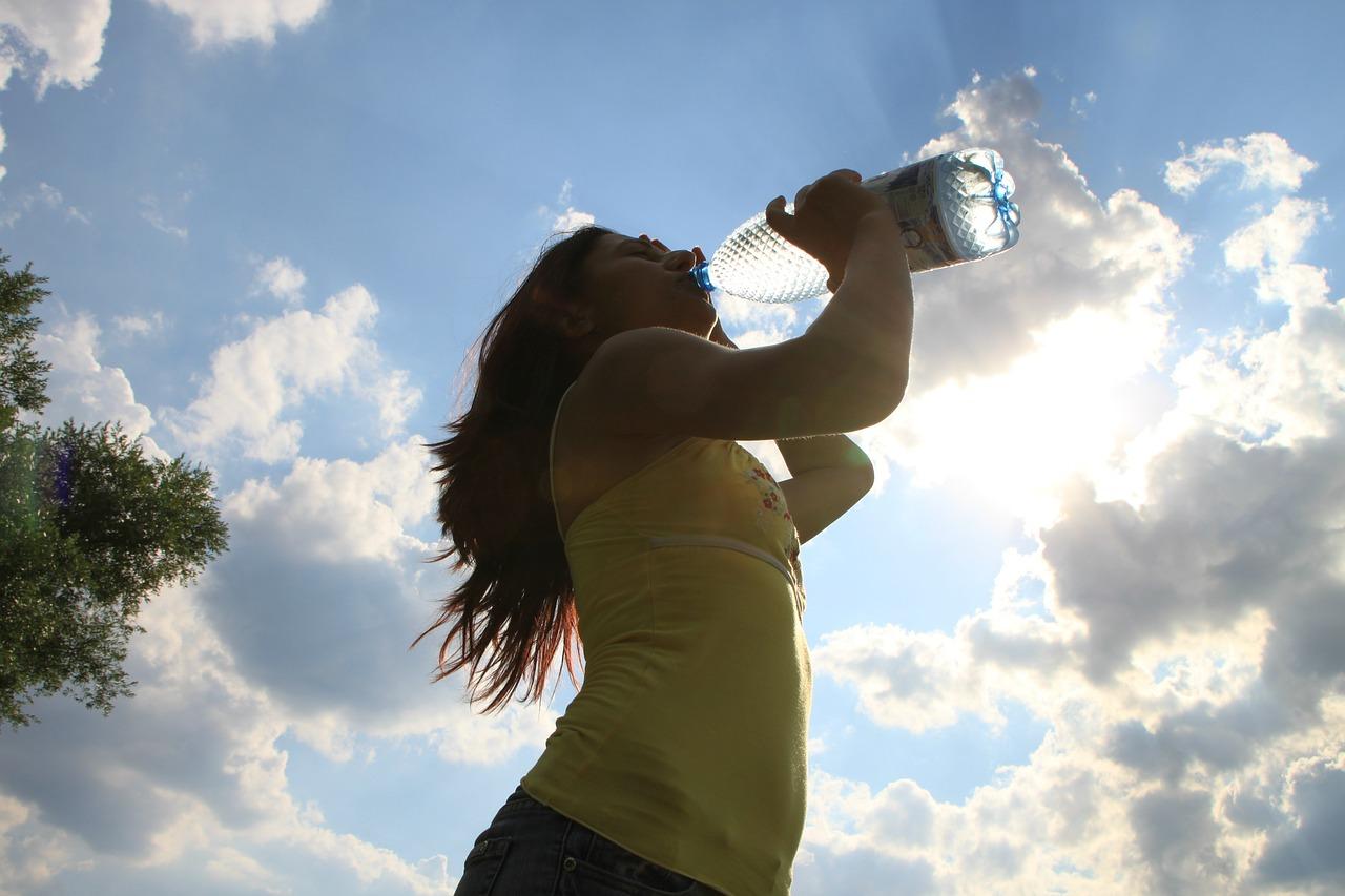 Ragazza all'aperto che beve acqua direttamente dalla bottiglia dopo aver fatto attività fisica.