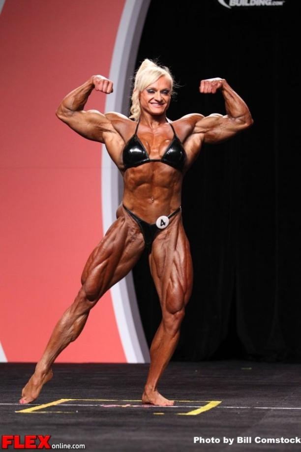 Immagine di una donna body-builder professionista sul palco durante una gara di body-building.