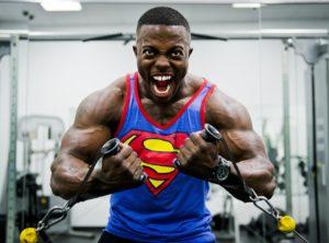 Body-builder in palestra che svolge un esercizio di trazione ai cavi indossando una canotta con lo stemma di superman.