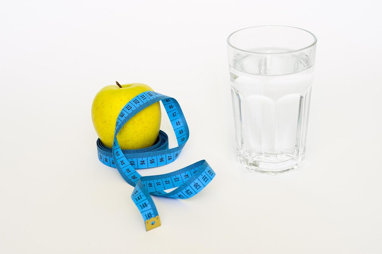Bicchiere in vetro pieno di acqua e mela circondata da un metro da sarto.