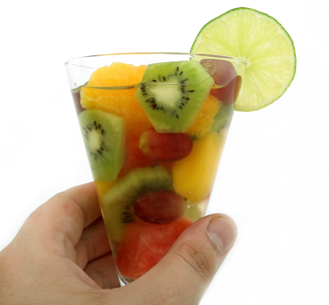 Bicchiere di acqua con frutta fresca tra cui kiwi, arancia, anguria e limone.