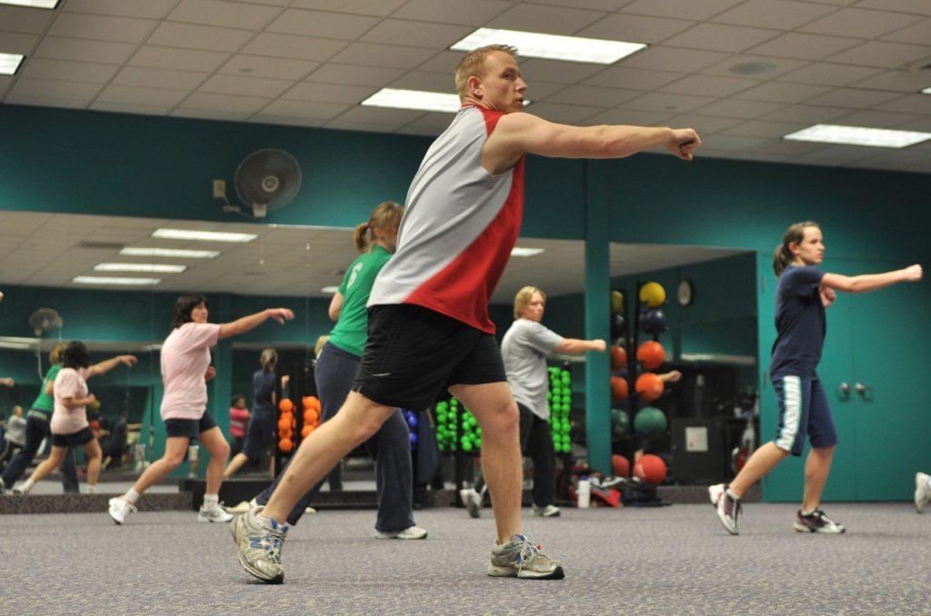 Rappresentazione di una sala fitness in cui l'istruttore sta tenendo un corso di ginnastica aerobica utile al dimagrimento.