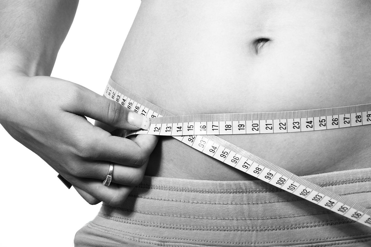Immagine focalizzata sulla pancia di una ragazza che si misura la circonferenza con un metro da sarto.