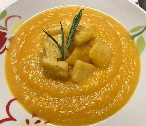 Foto della Ricetta della Crema di Zucca con Polenta croccante e erba cipollina, impiattata con un rametto di rosmarino