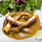 Foto della ricetta del polpo con salsa allo zafferano, impiattato con una insalata